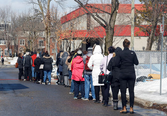Patients line up for coronavirus screening outside a temporary assessment center at the Brewer hockey arena in Ottawa