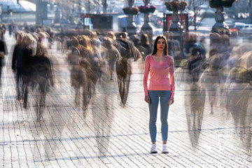 Obraz The young woman stands in the middle of crowded street - fototapety do salonu