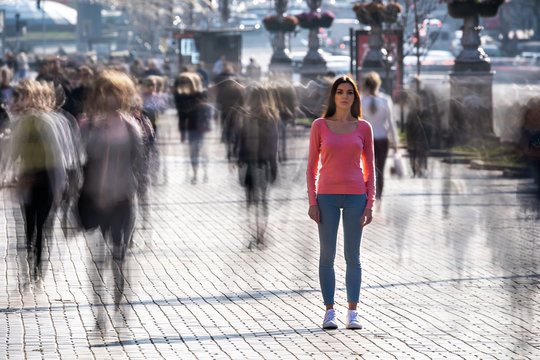The woman stands in the middle of crowded street