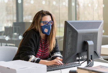 Coronavirus. Girl at the office sick with mask for corona virus. Business woman wear mask to...