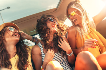 Three female friends enjoying traveling in the car. Sitting in rear seat and having fun on a road trip. Fotobehang