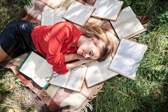 Young blond woman, wearing red shirt, lying sleeping on brown blanket. Creative flat-lay portrait, with person surrounded with many books. College student, tired on green grass after studying.