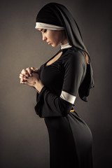young nun in a black robe prays
