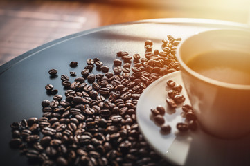 Canvas Prints Cafe Coffee and coffee beans on black table. Coffee beams closeup. Coffee theme. White cup on black table.
