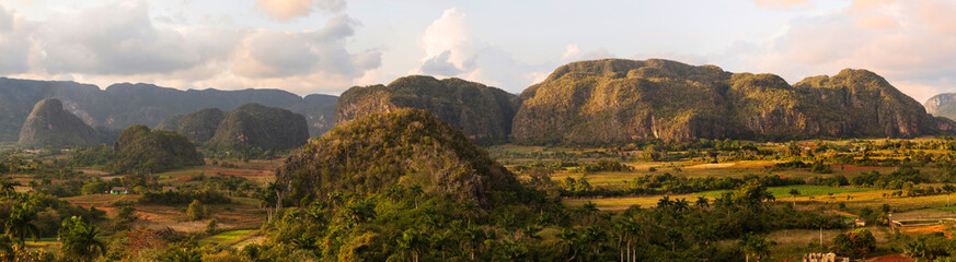 panoramic view of the valley of vinales cuba with mogotes and palm trees at sunset