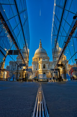 London, England - December 31 2020 - An early morning photo of St Paul's Cathedral with two glass fronted buildings reflecting it and forming a architectural canyon and jet trails in the sky.