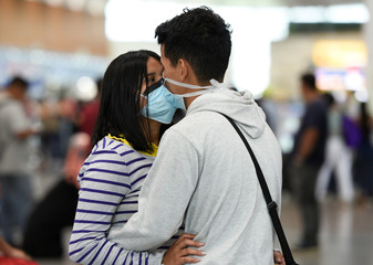 A couple wear protective face masks as they kiss, due to the outbreak of the coronavirus (COVID-19), at Jose Joaquin de Olmedo International Airport in Guayaquil