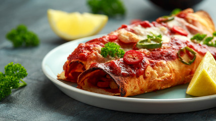 Baked Chicken fillets enchiladas with courgette, salsa sauce and cheese served with lemon wedges and chilies