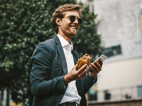 Young white colar or freelancer having a lunch on the go. Handsome man in a blue sute and sunglasses smiling holding smartphone and hamburger in his hands.