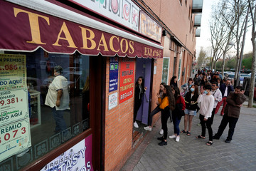People queue to buy tobacco at the Vallecas neighborhood, in Madrid