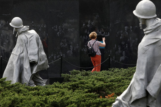A visitor takes a photo with an iPad at the Korean War Veterans Memorial along the National Mall, as Mayor Muriel Bowser has declared a State of Emergency due to the coronavirus disease (COVID-19) in Washington