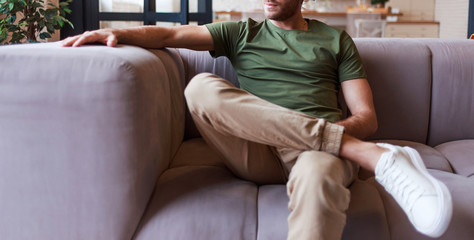 Casual handsome young man relaxing at home sitting on the couch. Man in blank khaki shirt for you mockup