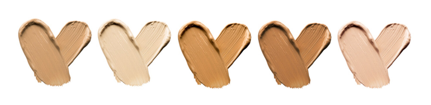 Foundation smears palette close-up. Heart shaped make-up smudge, smear. Cosmetic liquid bb cream beige color smudges, strokes. Colorful Liquid Make up concealer isolated on white background.