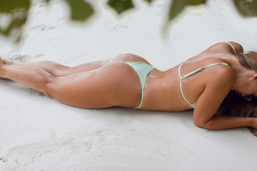 Slim sexy tanned girl in bikini laying on the white sand of tropical beach Fototapete