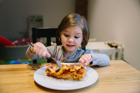 Little girl with a lasagne bolognese in a cafe