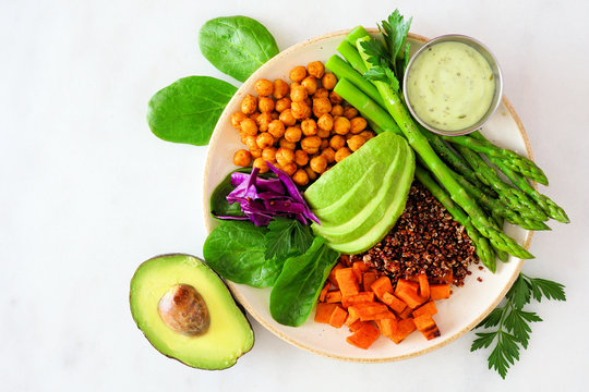 Healthy Buddha bowl with asparagus, quinoa, sweet potato, chickpeas and avocado. Overhead view over a white marble background.
