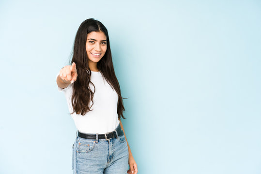 Young indian woman on blue background pointing to front with fingers.
