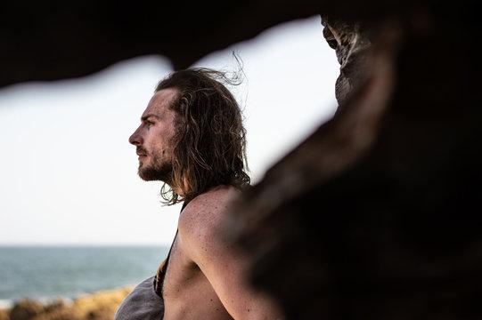 Männliches Model mit langen Haaren am Meer vor Felsen 2; Südafrika