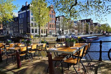 Fotobehang Amsterdam Restaurant tables lining the beautiful canals of Amsterdam under blue skies during springtime, Netherlands
