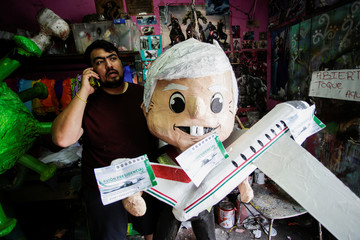 Artisan Dalton Ramirez holds a pinata of Mexico's President Andres Manuel Lopez Obrador holding a scale model of the presidential plane and mock lottery tickets for its raffle, at his workshop in Reynosa