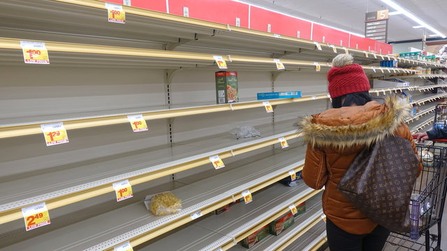 A shopper in front of empty pasta shelves in a grocery store. People are hoarding food to prepare for the worst in Coronavirus scare. Photo taken in Carlsbad, CA / USA on March 13, 2020.