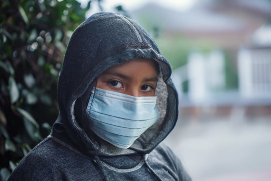 Latino 9 year old girl or student wearing a hoodie sweatshirt and medical face mask to prevent the spread of infectious diseases.