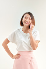 Cheerful young woman talking on mobile phone isolated on white background
