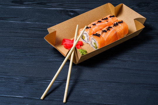 Traditional Japanese food. Sushi, rolls and chopsticks for sushi on a dark background. Rolls in box to go.