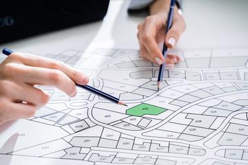 Fototapeta Human Hand Holding Pencil Over Cadastre Map