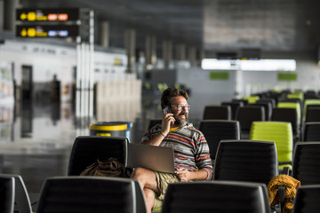 Adult man travel at the airport sit down at the gate waiting for his airplan flight - delay conncept and people working everywhere with laptop computer technology - caucasian male traveling
