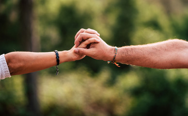 Love and team concept with woman and man hands holding together - help and cooperation people - green defocused background - together forever care each other lifestyle Wall mural
