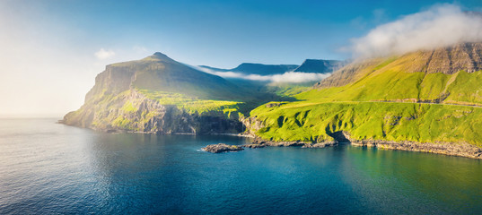 View from flying drone. Misty morning scene of Vagar island. Colorful summer scene of Faroe Islands, Kingdom of Denmark, Europe. Traveling concept background