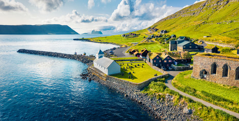 Foto op Aluminium Noord Europa View from flying drone. Aerial summer view of Kirkjubour villagewith Hestur Island on background. Picturesque morning scene of Faroe Islands, Denmark, Europe. Beauty of nature concept background.