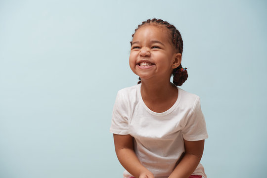 Portrait of cute little girl dressed for sport. Pale blue background.