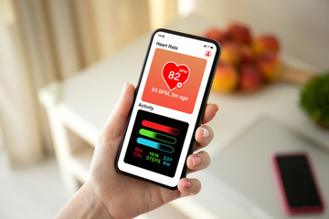 female hand holding phone with app heart and activity
