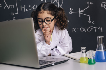 little scientist girl looking to the computer
