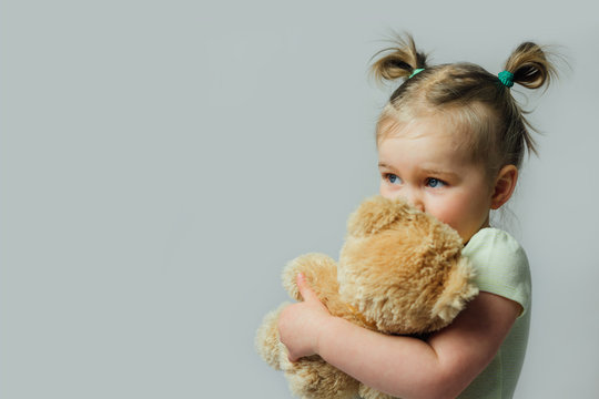 Portrait of baby toddler holding soft toy looking away on gray background. Children rights concept. Free space for text.