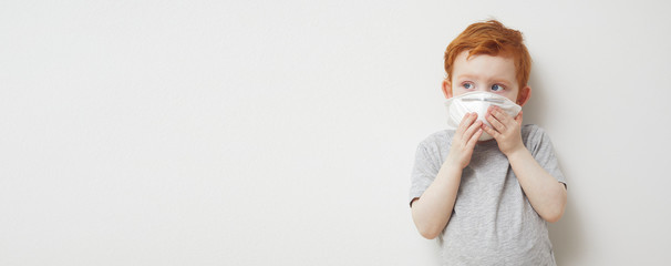 Little boy trying to stay healthy by wearing a mask to protect him against corona virus covid-19 / 2019-nCov while looking at copyspace Fototapete