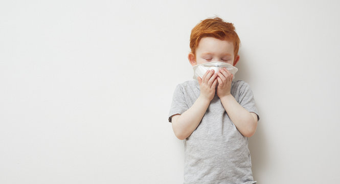 Little boy trying to stay healthy by wearing a mask to protect him against corona virus covid-19 / 2019-nCov while closing his eyes
