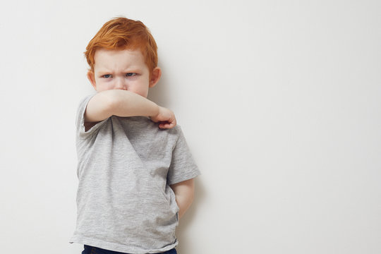 Young boy is afraid to get sick from the corona virus covid-19 / 2019-nCov and is showing how you should cough into the sleeve, while looking to the side