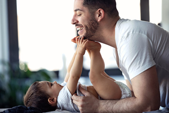 Smiling young father has fun with little baby while changing his nappy at home.