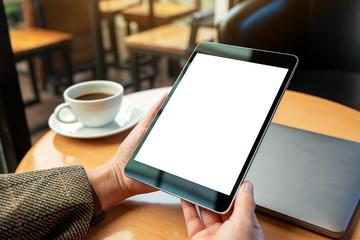 Mockup image of a woman holding black tablet pc with blank white screen with laptop and coffee cup...