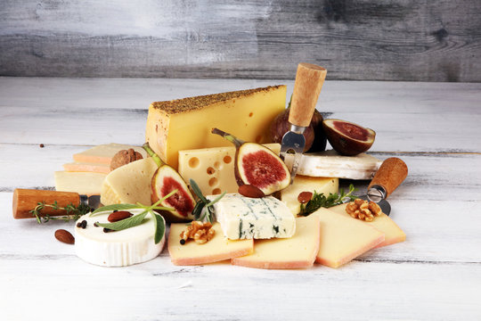 Cheese plate served with figs, various cheese on a rustic table