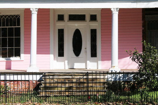 abandoned pink southern plantation front porch retro door gate