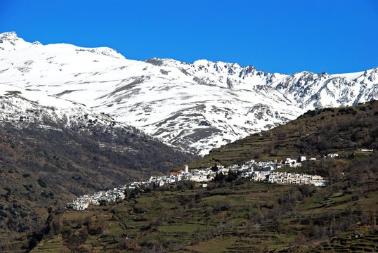 View of the town looking towards the snow capped mountains of the Sierra Nevada, Pampaneira, Spain.