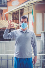 caucasian man wearing protective masks. Sick man with flu wearing mask and saying it is ok using hand