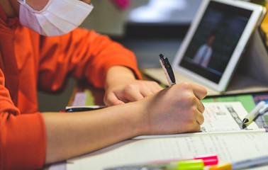 マスクをした子供が自宅でタブレット学習するシーン