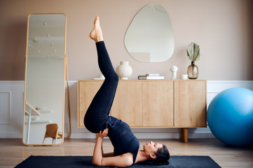 Woman practicing advanced yoga at home
