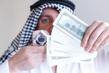 Arab sheikh from Arabia saudi, Emirates holds in hands drop of oil of Brent brand in crystal cube. Pack of hundred dollars bills.Crisis in financial market,falling,rising prices,quotes, exchange rate