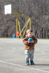 Little toddler boy, playing with ball on playground